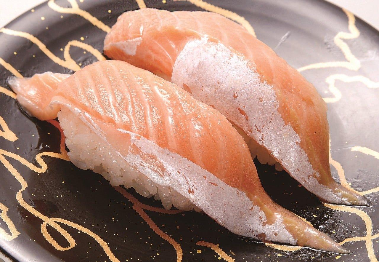 黒いお皿にサーモンのお寿司が乗っている