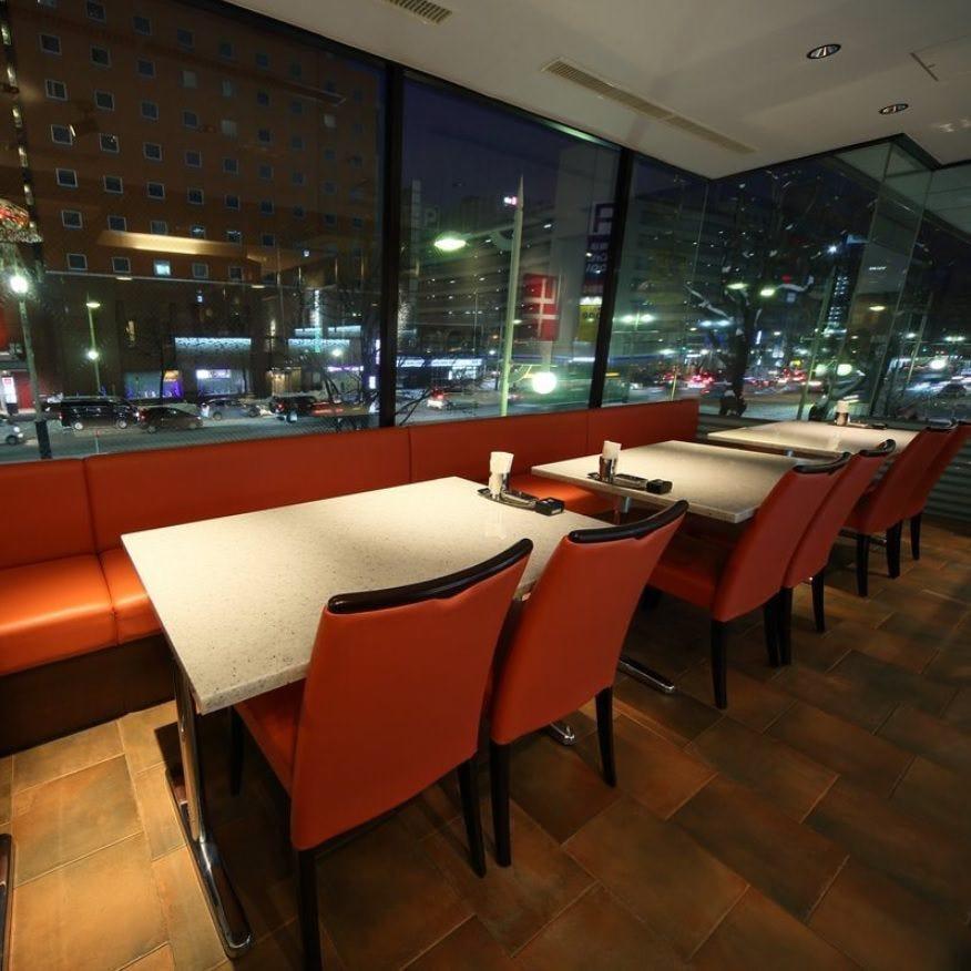 白いテーブルと赤い椅子が窓際に並んでいる