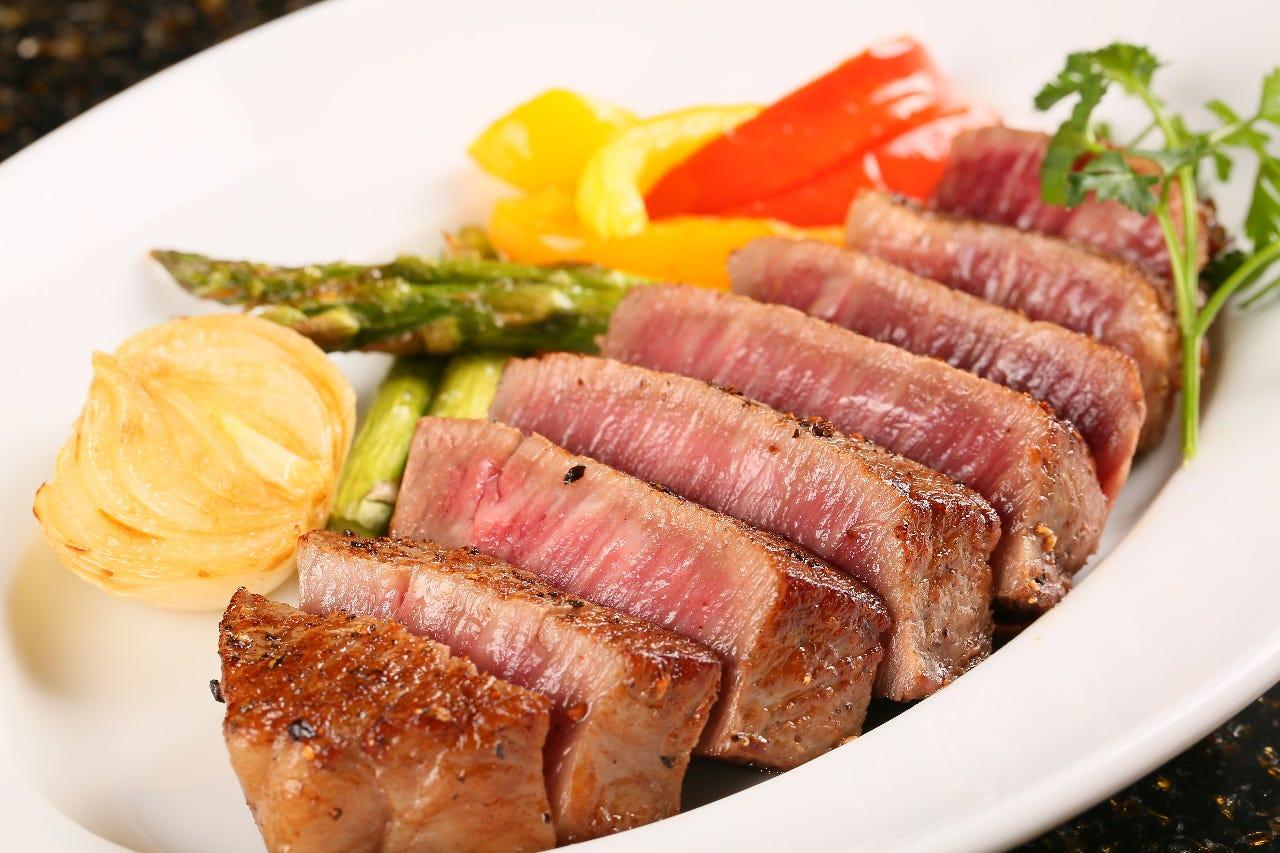 白いお皿にレアの肉と野菜がもられている
