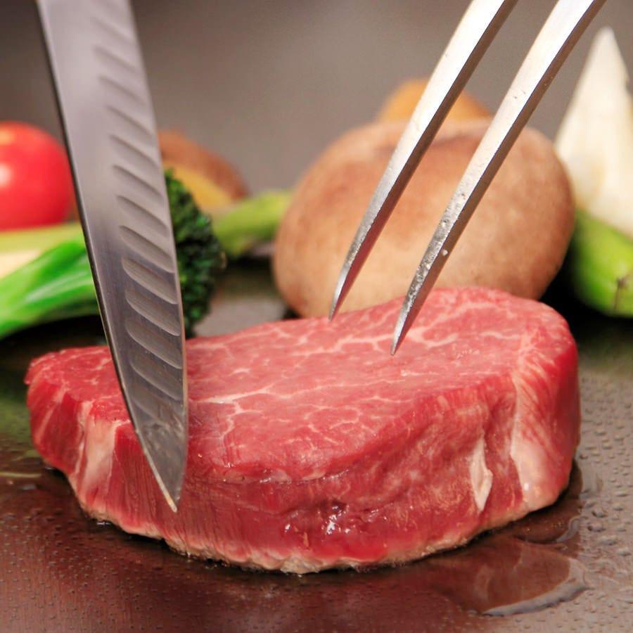 赤身の肉をナイフで切ろうとしている