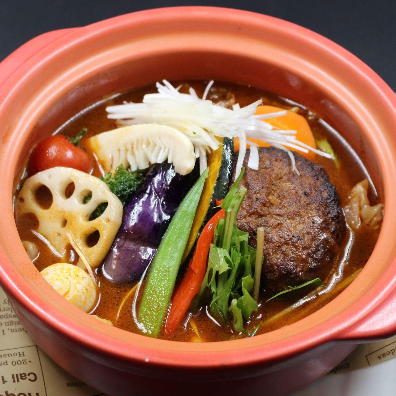 茶色い器にハンバーグと野菜が盛られている