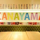 """壁に書かれた""""KANAYAMA""""の文字と、鮮やかなグリーンのソファが目を引くフォトジェニックな空間です♪"""