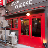 グレーの壁に赤い扉が鮮やかな当店外観