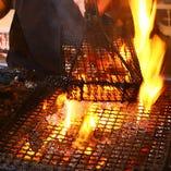 豪快な火柱を上げて焼き上げる、さつま知覧鶏もも肉の炙り焼は、迫力満点!