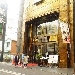 金色の5階建てビルが見えます。「菜香新館」に到着です。
