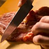 〈熟練の技で調理〉 熟練の職人が丁寧に鶏肉を調理します