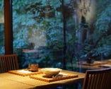 ライトアップされた静寂の夜の森が窓辺に映る