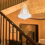 シャンデリアが煌く重厚感溢れるホテルフロント。その奥が店内。