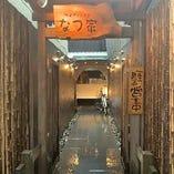 奥行きあるアプローチに石だたみ、塀に黒竹と個性的な門構えです。開店前に水打ちをしお客様を優しくお迎えするエントランス。