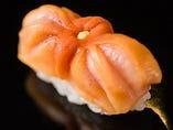 身を傷めないようにと、丸く包んだ布巾の上で包丁を入れる赤貝