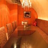 天井のシャンデリアや高級感を感じられるベルベット生地のソファー