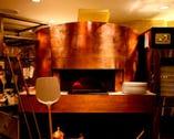 オープンキッチンの店内メインフロア。黄金の薪窯が光る。