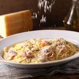 テーブルで削るパルミジャーノレッジャーノチーズのカルボナーラ