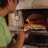 香ばしくてふっくらした石窯焼きピザは当店の名物メニューです。