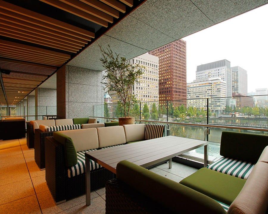 東京のオフィスビルと皇居を囲む水辺とグリーンを望むテラス席