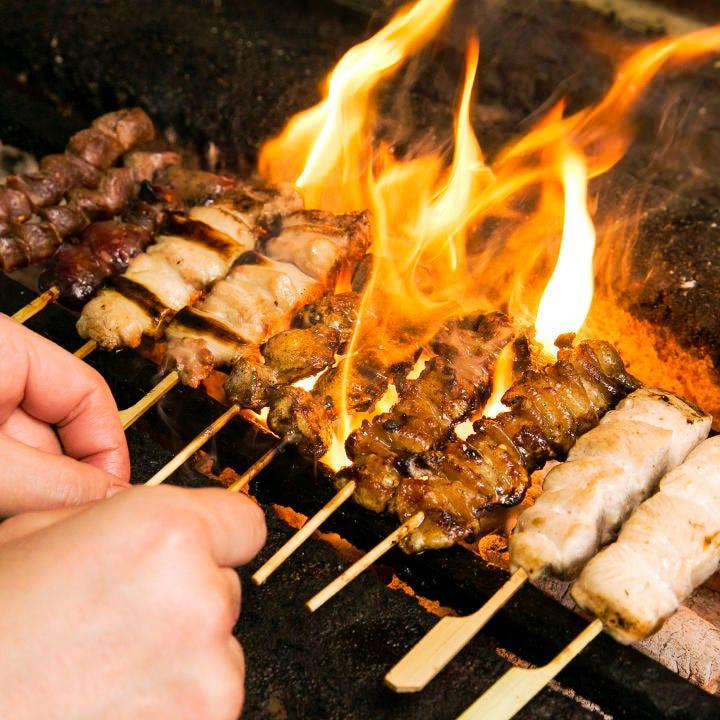 炭火で炙る名古屋コーチンの串焼き