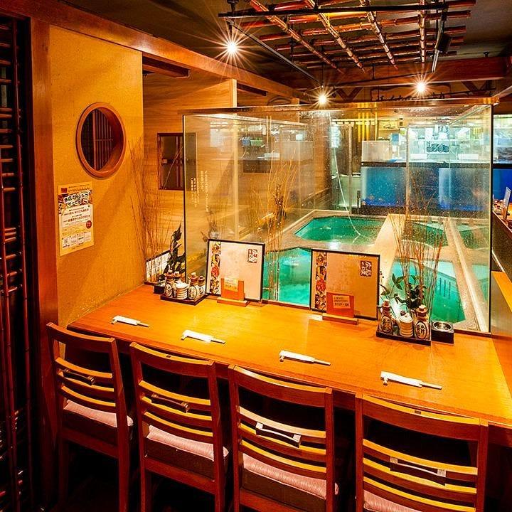 イカや鯖の泳ぐ大きな生簀を望むカウンター席でゆったりお食事を