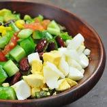 アボカド、オリーブ、トマトなど7種類の具材の虹が乗った「レインボー コブサラダ」。