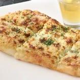 名物!ゴルゴンゾーラのナンピザ。店主イチオシ、誰もが頼む一品!ナンの食感と後がけ蜂蜜がgood!