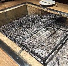 各卓に設置された囲炉裏で肉を焼く