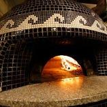 ピッツァは薪窯で丁寧に焼き上げます。