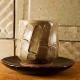 宮崎県・綾町の陶器:当店カウンター後の陶製タイル、ふすまの取っ手、洗面台、こだわり壱の写真にあります銘板、そして当店の器のほとんどは宮崎県・綾町の元町窯、練り込みの技法で有名な一ツ葉焼き、お客様のご要望もありそれらの器を店内に陳列しています。手造りの器は見ているだけでも楽しく心を豊かにしてくれます。