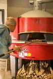 お店に入ってまず目に付く真っ赤な薪窯。