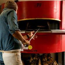 腕自慢のピザ職人が焼いた薪窯ピザ。