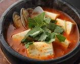 純豆腐チゲ】  アサリの煮汁をベースとしたの特製スープに、豚肉・豆腐・キムチ・玉ねぎなどが入った辛口鍋です。具材としてもしっかりアサリを加わり旨味が超豊富!熱々