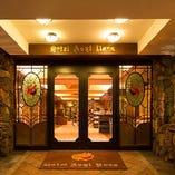 ホテルの正面玄関を入られまして、フロント前エレベーターで2階へおあがり下さい。ホテル1階にはお土産ショップもございます。また、この自動ドアに向かって右手に外階段があり、こちらから直接レストランにお上がりいただくこともできます。