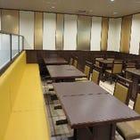 黄色い片面ソファベンチシートが鮮やかな、ホール席