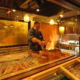 職人の熟練の技で豪快に焼き上げる炭火焼を目の前で楽しむ。