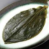 【ミョンイナムル(行者ニンニクの醤油漬け)】ユリ科の植物。韓国では命のナムルと呼ばれ、脂肪燃焼効果があると言われています。疲労回復効果があるビタミンB1活性を持続させるアリシンを含んでいます。その他たくさんの効能があるとして注目されている行者ニンニクにお肉を巻いて食べると味も健康にも最高!!
