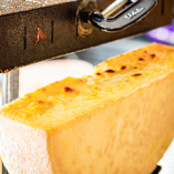 店内で焼き上げたラクレットチーズを目の前でかけて提供します。