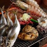 〈炉端焼き〉 新鮮魚介や地鶏を囲炉裏で焼いて楽しむスタイル