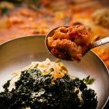 韓国のりをバサッと盛った丼ぶりのご飯に、 海老やイイダコ、ホルモンなどの具材がたっぷり入った熱々スープを入れて食べるのが本場流