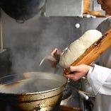 成熟したタネを麺包丁で削ると同時に、鍋に飛ばし入れる刀削麺