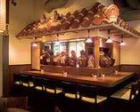 カウンターには古酒甕が並ぶ 泡盛は27銘柄
