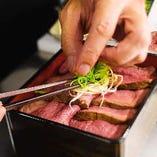 均一な赤みを帯びたステーキを繊細な手さばきで美しく盛り付け