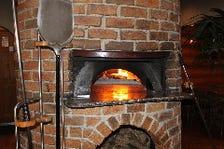 薪で焼き上げる薄焼きピッツアは絶品