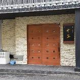 白い外壁と大きな木製のドアが目印です