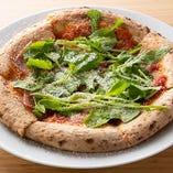 たっぷりの生ハムに、ルッコラもたっぷりと盛り付けた「生ハムとルッコラのピザ」。ハムの塩気と葉野菜の爽やかな味わいが、口の中で見事に調和します。