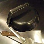 創業者・藤岡重次が生み出したキャップ。油のハネをふせぐためにフライパンをかぶせたことから生まれました。いまでは専用のものもありますが、写真は神戸本店にあるフライパンの柄を曲げて作っていた当時のキャップ。