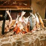 まず目に入る、まる秀特注の炉。炭火と焼き物との距離で火加減を調節する職人技をじっくりと。