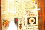 雑誌で紹介された広告やメニューリストが張られています。
