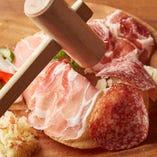 人気の前菜「生ハムとサラミのシャルキュトリボード」は、コールドカット、マーク家に伝わる伝統レシピによる特製ザワークラウトとピクルスの盛り合わせ。ドーム状のクラッカーの上にトッピングし、木槌でクラッカーを割って楽しむという演出も楽しい人気の一品です。