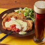 ビールの街・ミュンヘン発祥のポークカツレツ「シュニッツェル」。本場のドイツビールと合わせればそのおいしさはより一層際立ちます。黄金色のサクサク衣とジューシーな肉の旨みを注ぎたてのクラフトビールとどうぞ。