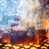 名物鶏の炭焼きは、炎と煙を 巻き込むようにして焼き上げる!