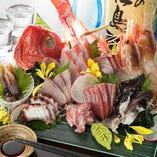 朝獲れの旬鮮魚でお造りする刺身は、魚串と並ぶ自慢の逸品です。金目鯛や本まぐろ、天然ブリの他、生のボタン海老やホタルイカにトリ貝など、色々な種類の魚介をたくさん召し上がっていただけるよう、日替わりでご用意しています。醤油を弾くほど脂がのり、甘みが凝縮された刺身をご堪能ください。単品でもどうぞ。