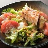厚切りベーコンと温泉卵で愉しむ『シーザーサラダ』は、ボリューム満点の一皿です。